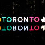 The TORONTO sign at Nathan Phillips Square lit in the Italian flag colours at night.