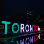 The TORONTO sign at Nathan Phillips Square lit in the Italian flag colours at night, for Villa Charities' 50th anniversary.