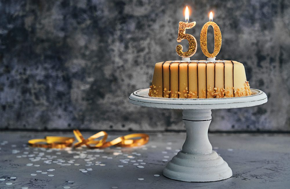 Birthday cake on a cake stand topped with a candle shaped like the number