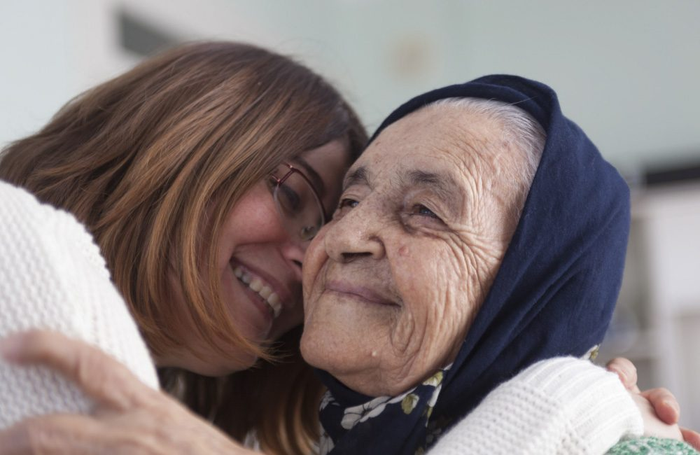 Two people embrace and hug; one of them is a senior.