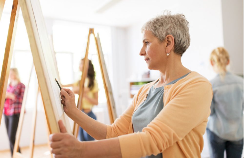 An art workshop with adult students painting on a canvas.