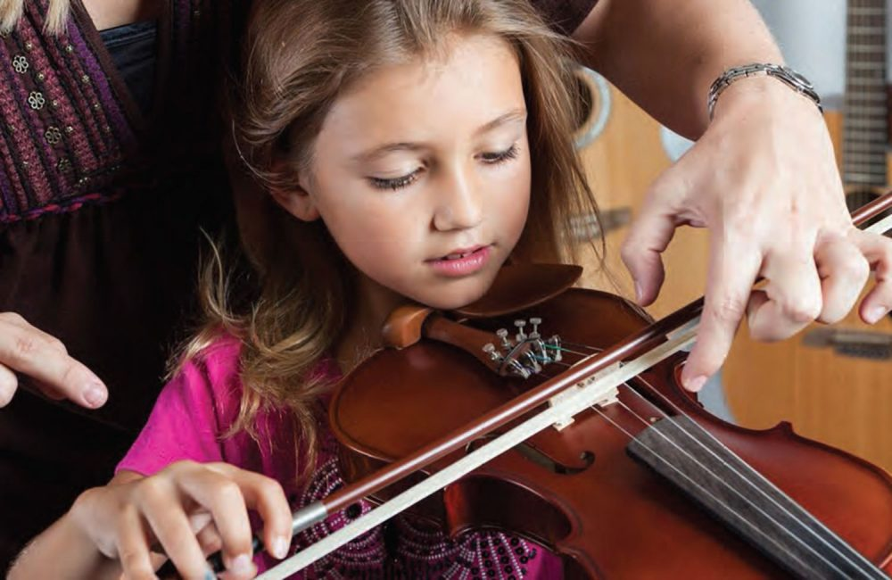 A music teacher instructs a student how to play the violin.