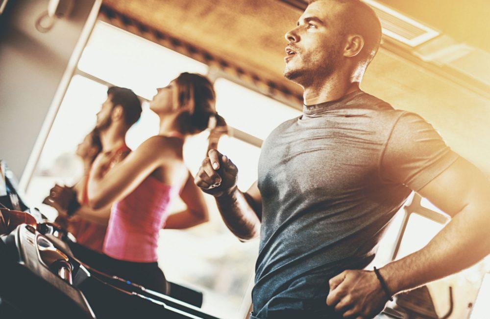 Group of people running on treadmills.