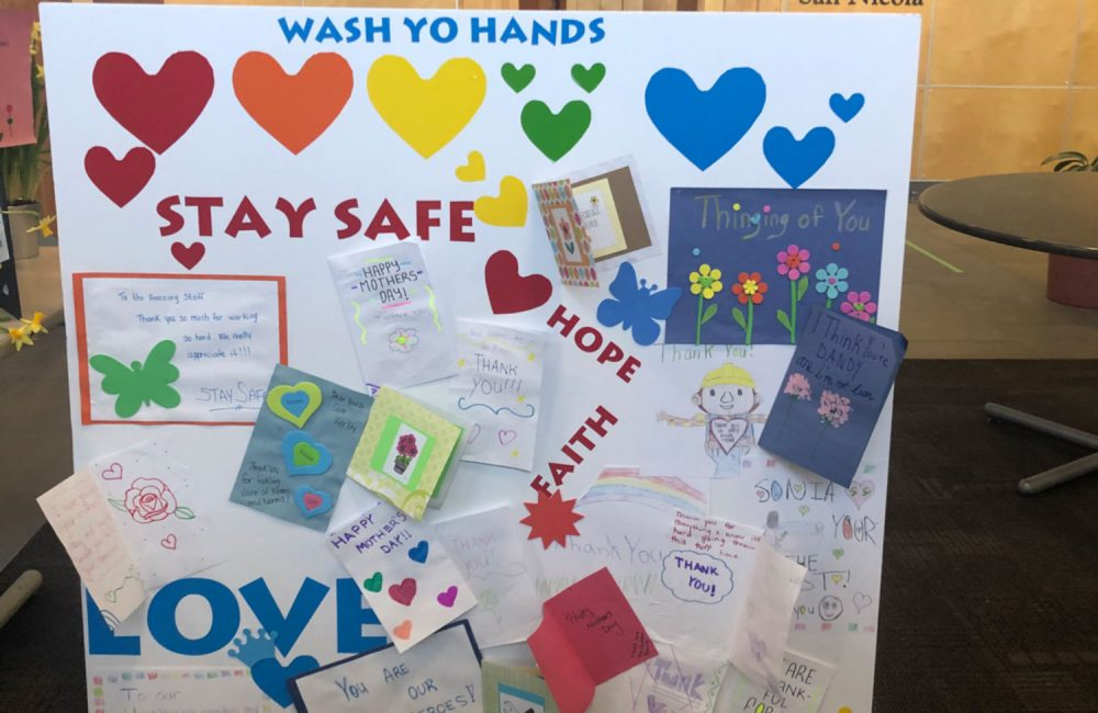A poster board featuring coloured hearts, written notes, and the words