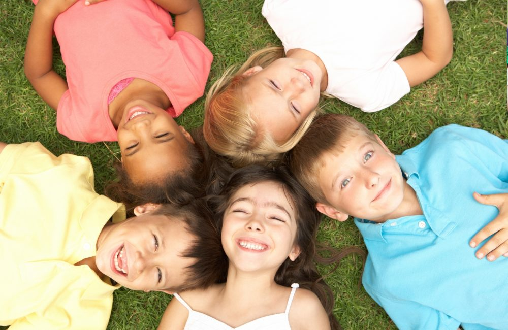 A group of children laying down in a circle on the grass.