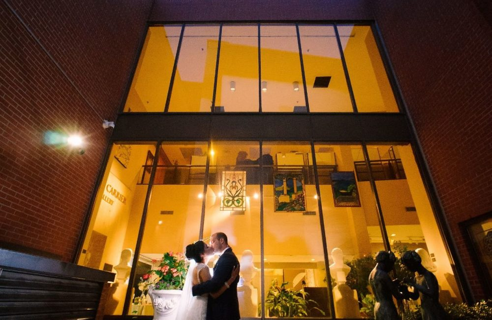 A bride and groom pose in front of the Joseph D. Carrier Art Gallery rotunda at night.