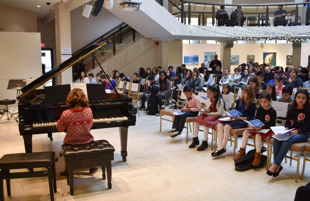 A student plays the piano at a Columbus School of Music recital.