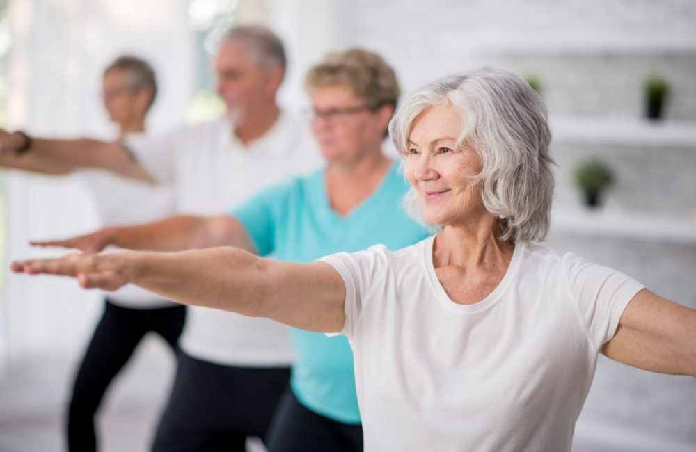 A group of seniors exercising in a yoga class.