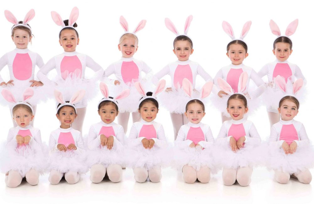 A group of young DanzArts Toronto dance students wearing bunny costumes posing in two rows for a photo.