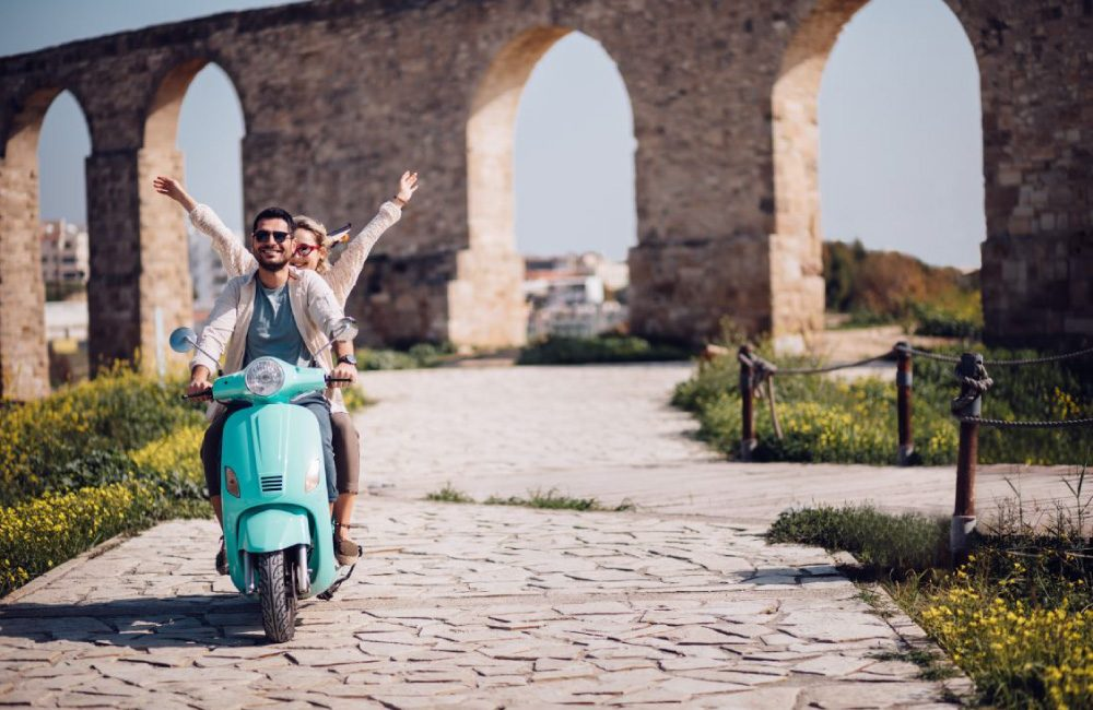 Two people riding together on a light blue vespa.