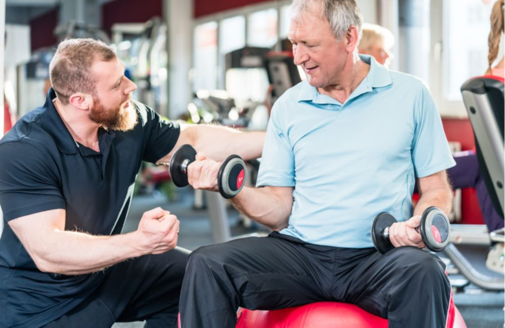 A personal trainer helps a senior lift dumbbells at a gym.