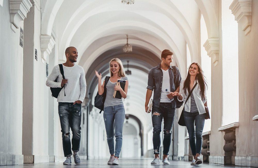 A group of students walking along an outside corridor.