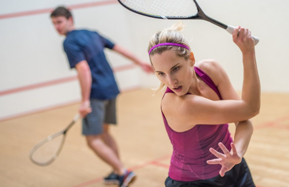 Two people playing squash in a court.