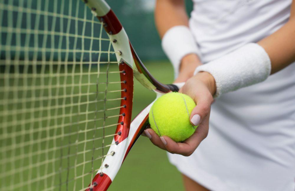 A female holds a tennis racquet and a tennis ball.